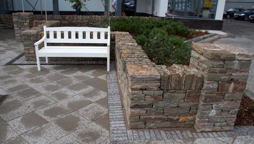 Мощение из недорогой бетонной плитки не смотрится дёшево за счёт контраста с качественно сложенной стенкой из камня.