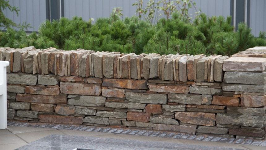 Крышка стены сложена из вертикально установленных камней