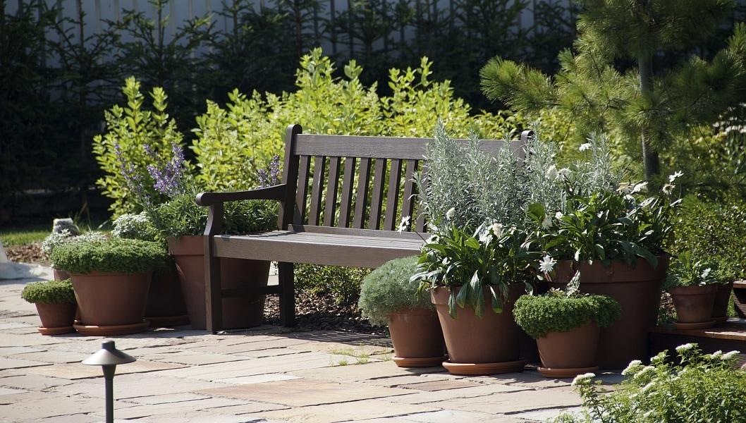 Место для отдыха. Классическая массивная скамья в окружении терракотовых горшков с декоративными и пряными травами