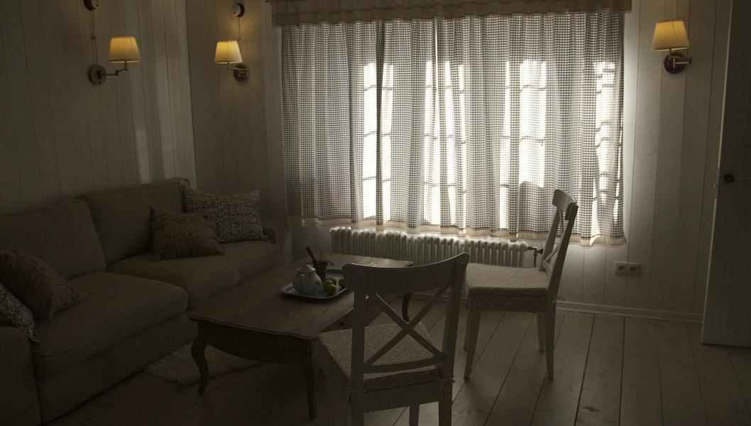 Деревянные рамы с расстекловкой, простая мебель в гостиной