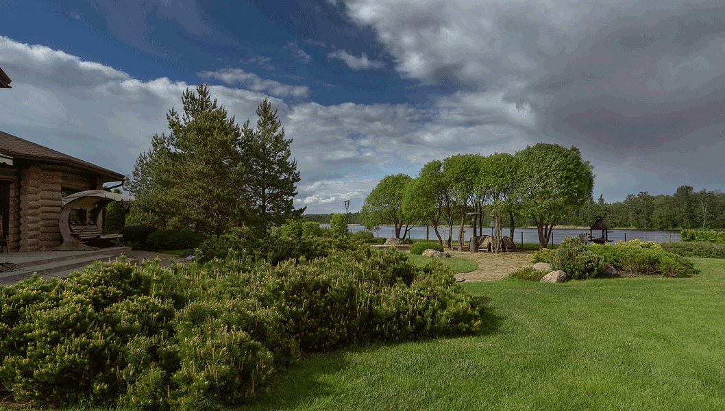 Под тенью шаровидных ив (Salix fragilis 'Bullata') расположена площадка с круглым столом
